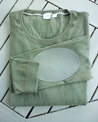 green jumper with sage green elbow patch