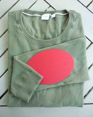 green jumper with red elbow patch
