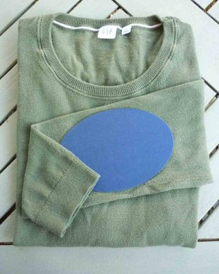 green jumper with blue elbow patch